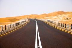 Carretera de asfalto negra de enrrollamiento a través de las dunas de arena del oasis de Liwa, United Arab Emirates Fotografía de archivo