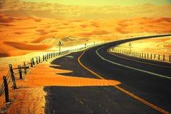 Carretera de asfalto negra de enrrollamiento a través de las dunas de arena del oasis de Liwa, United Arab Emirates Foto de archivo