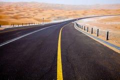 Carretera de asfalto negra de enrrollamiento a través de las dunas de arena del oasis de Liwa, United Arab Emirates Imagen de archivo libre de regalías