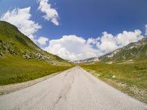 Carretera de asfalto recta rodeada por las montañas con las nubes en el fondo imagenes de archivo