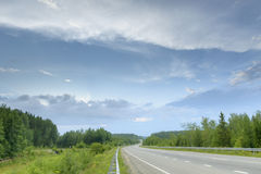 Carretera de asfalto a través del bosque con las nubes, verano Imagen de archivo