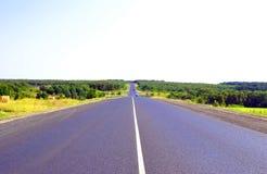 Carretera de asfalto a través del campo verde Imagen de archivo libre de regalías