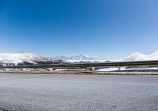 Carretera de asfalto vacía con la montaña de la nieve Imagenes de archivo