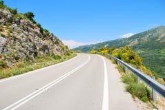 Carretera de asfalto vacía en las colinas verdes Imagen de archivo libre de regalías
