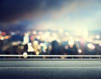 Carretera de asfalto y ciudad borrosa Fotografía de archivo libre de regalías