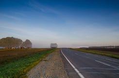 Carretera de asfalto y prado verde en la niebla en el amanecer en verano y s Fotografía de archivo libre de regalías