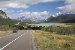 Carretera de la bobina al lado de un lago mountain - Alberta, Canadá Foto de archivo
