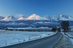 Carretera debajo de las montañas alpinas en día de invierno Foto de archivo