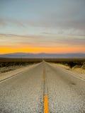 Carretera del desierto en la puesta del sol Fotografía de archivo libre de regalías
