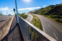 Carretera del puente de la subida de la colina de los jinetes de la raza de ciclo Imagen de archivo libre de regalías