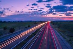Carretera en la oscuridad con el cielo hermoso Imagen de archivo