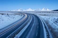 Carretera libre en tiempo de mañana y montañas nevadas en horizonte Fotos de archivo