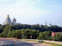 Carretera más allá del monasterio con un alto templo en un día soleado fotografía de archivo