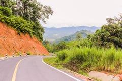 Carretera nacional abajo de la colina, montaña lejos a continuación Fotos de archivo libres de regalías
