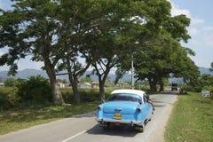 Carretera nacional cubana con el coche americano viejo Foto de archivo