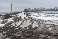 Carretera nacional sucia entre los campos agrícolas en Ucrania central en el día de invierno melancólico Fotografía de archivo
