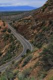 Carretera que teje a través de cepillo sabio y de la roca roja de Utah Foto de archivo