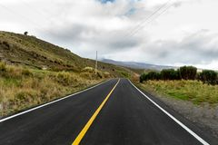 Carretera rural en el medio de una montaña con el cielo nublado fotografía de archivo