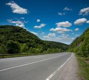 Carretera vacía de la carretera de asfalto en las montañas boscosas, en el cielo Fotos de archivo