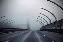 Carretera vacía en niebla gris de la mañana ningunos coches Imagenes de archivo