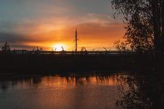 Carretera y líneas eléctricas en el fondo de la puesta del sol, visión desde el riverbank fotografía de archivo