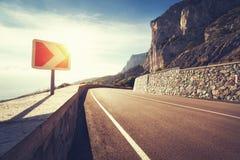 Carretera y señal de tráfico de asfalto en montañas en la salida del sol Imagenes de archivo