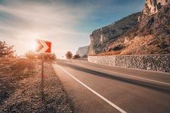 Carretera y señal de tráfico de asfalto en montañas en la salida del sol Fotos de archivo
