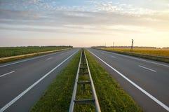 Carreteras a lo largo de un campo de girasoles Fotos de archivo libres de regalías
