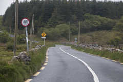 Carreteras nacionales irlandesas estrechas típicas con 100 kilómetros por límite de la hora Foto de archivo