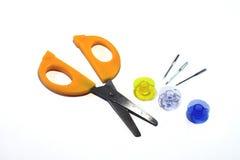 Carretes, agujas y tijeras con las manijas anaranjadas en el fondo blanco Foto de archivo libre de regalías