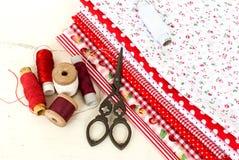 Carretes coloreados de la tela del hilo y de las tijeras para coser Foto de archivo