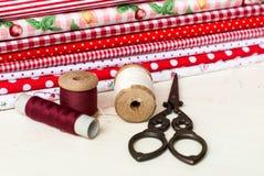 Carretes coloreados de la tela del hilo y de las tijeras para coser Imagenes de archivo