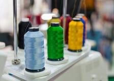 Carretes coloridos de hilos en la máquina profesional para aplicar el bordado fotografía de archivo