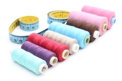 Carretes coloridos de la cinta métrica del hilo en el fondo blanco Fotos de archivo