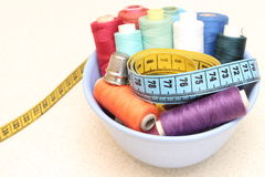 Carretes coloridos del hilo, de la cinta métrica y del dedal Fotos de archivo libres de regalías