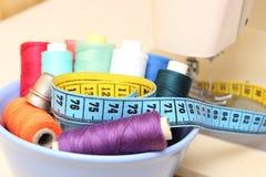 Carretes coloridos del hilo, de la cinta métrica y del dedal Foto de archivo libre de regalías