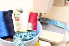 Carretes coloridos del hilo, de la cinta métrica y del dedal Imagenes de archivo