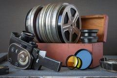 Carretes con las películas en una caja de madera, lente y una cámara de película vieja Imagen de archivo