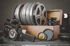 Carretes con las películas en una caja de madera, lente y una cámara de película vieja Imagenes de archivo