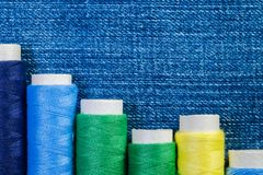 Carretes de hilos verdes, amarillos y azules en el dril de algodón azul imagen de archivo