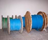 Carretes de madera industriales grandes de alambres azules y verdes en piso gris Foto de archivo