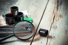 Carretes de película de la foto, pila de fotos y lupa Fotografía de archivo