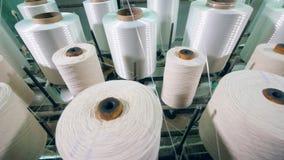 Carretes del hilado en las hiladoras en una planta de materia textil almacen de metraje de vídeo