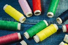 Carretes del hilo de coser azul, blanco, del rosa, rojo y verde en el dril de algodón imagen de archivo