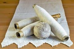 Carretes del vintage con los hilos naturales del lino y mantel hecho a mano del cordón en un fondo de madera Fotos de archivo