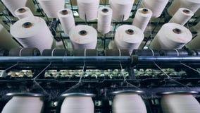 Carretes que hacen girar en las máquinas de la fábrica, fibra blanca que arrolla metrajes