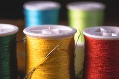 Carretes vivos borrosos de las bobinas de los hilos de los colores, diseño de concepto de costura industrial fotos de archivo libres de regalías