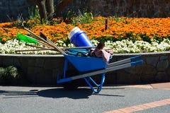 Carretilla con las herramientas que cultivan un huerto en jardín de flores Imágenes de archivo libres de regalías
