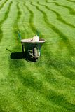 Carretilla con un poco de equipo que cultiva un huerto en una hierba verde del corte fresco imagenes de archivo