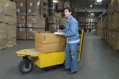 Carretilla de funcionamiento del hombre en Warehouse Imágenes de archivo libres de regalías